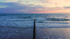 Nubes coloridas de la puesta del sol sobre bahía de la rebeca en Reino Unido almacen de metraje de vídeo