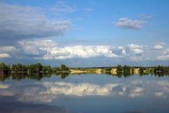 nubes de cúmulo del paisaje con la reflexión en agua Imagenes de archivo