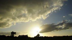 Nubes de cúmulo en la puesta del sol que corre rápidamente sobre el campo en timelapse Siluetas de las casas, granjas, árboles en almacen de video