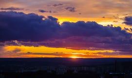 Nubes de cúmulo en la puesta del sol sobre la ciudad Fotos de archivo