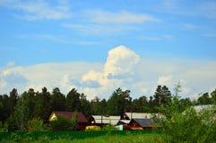 Nubes de cúmulo hermosas en el cielo azul Sobre casas de madera rurales Paisaje del VERANO Foto de archivo libre de regalías