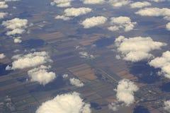 Nubes de cúmulo sobre los campos de la opinión del aeroplano foto de archivo libre de regalías