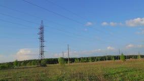 Nubes de funcionamiento en el fondo de líneas eléctricas de alto voltaje en el campo Revestimientos del tiempo almacen de video