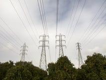 Nubes de la energía eléctrica y árboles anaranjados Foto de archivo