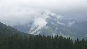 Nubes de la mañana que suben encima de las cuestas alpinas metrajes