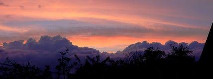 Nubes de la puesta del sol sobre árboles Foto de archivo libre de regalías