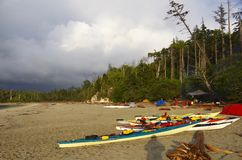 Nubes de lluvia sobre la playa, kajaks en el primero plano fotos de archivo