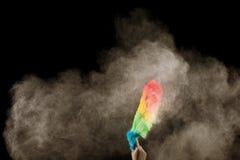 Nubes de polvo de la mano que barren en el aire Las amas de casa están sacando el polvo con las plumas plásticas foto de archivo