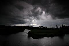 Nubes de tormenta negras sobre un río Foto de archivo