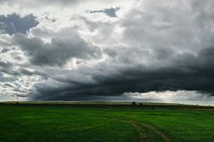 Nubes de tormenta oscuras sobre el campo de hierba verde Imagen de archivo