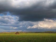 Nubes de tormenta sobre un campo con un pajar fotos de archivo