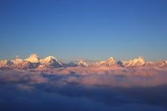 Nubes del balanceo y paisaje de la montaña de la nieve de la salida del sol imagen de archivo