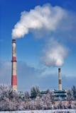 chimeneas de la fábrica con las nubes del humo blanco Imágenes de archivo libres de regalías