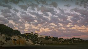 Nubes delicadas sobre casas de playa en la puesta del sol imagen de archivo