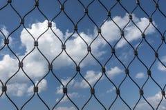 Nubes detrás de la cerca de la malla Imágenes de archivo libres de regalías
