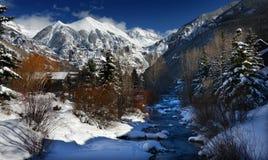Nubes dramáticas del invierno, nieve alpina cristalina, y corriente helada en Rocky Mountains, Colorado imagenes de archivo
