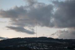 Nubes dramáticas sobre torre de difusión encima de la colina D?a a la noche Cielo de la puesta del sol Cielo de oscurecimiento po imágenes de archivo libres de regalías