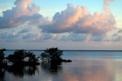 Nubes en colores pastel sobre el agua reflectora Foto de archivo libre de regalías