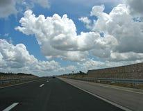 Nubes en una carretera Imagen de archivo libre de regalías