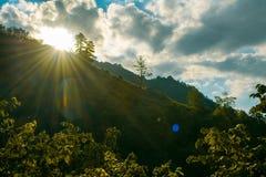 Nubes entre el sol y la casa sola en la colina fotografía de archivo