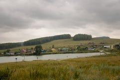 Nubes grises pesadas en el cielo frío del otoño sobre pueblo con las pequeñas casas lejos en las montañas y los campos Pocos fluj Foto de archivo libre de regalías