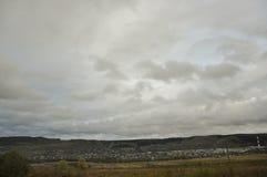 Nubes grises pesadas en el cielo fr?o del oto?o sobre pueblo con las peque?as casas lejos en las monta?as y los campos travelling fotos de archivo