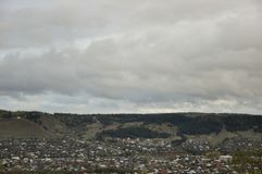Nubes grises pesadas en el cielo fr?o del oto?o sobre pueblo con las peque?as casas lejos en las monta?as y los campos travelling foto de archivo