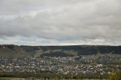 Nubes grises pesadas en el cielo fr?o del oto?o sobre pueblo con las peque?as casas lejos en las monta?as y los campos travelling imagenes de archivo