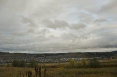 Nubes grises pesadas en el cielo fr?o del oto?o sobre pueblo con las peque?as casas lejos en las monta?as y los campos travelling foto de archivo libre de regalías