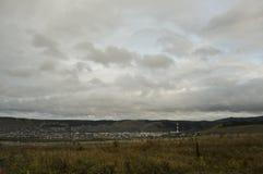 Nubes grises pesadas en el cielo fr?o del oto?o sobre pueblo con las peque?as casas lejos en las monta?as y los campos travelling fotos de archivo libres de regalías