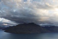 Nubes gruesas que pasan sobre gama de montañas Fotos de archivo
