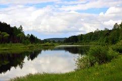 Nubes hermosas reflejadas en el río Verano en Siberia Imagenes de archivo