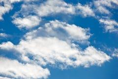 Nubes lanosas en el cielo azul fotos de archivo