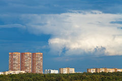 Nubes lluviosas azul marino sobre casas de varios pisos Fotos de archivo libres de regalías