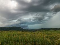 Nubes lluviosas sobre campos verdes fotografía de archivo
