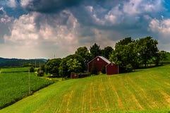 Nubes oscuras sobre los campos en el condado de York meridional rural, PA de un granero y de granja Foto de archivo