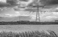 Nubes oscuras sobre una fila de los pilones del poder foto de archivo