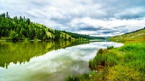 Nubes oscuras y montañas circundantes que reflejan en la superficie lisa del agua del lago Trapp imagen de archivo