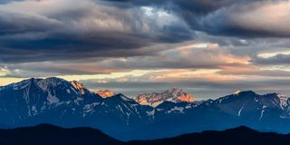 Nubes pesadas de la puesta del sol en las montañas Imágenes de archivo libres de regalías