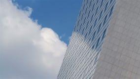 Nubes que pasan por un edificio de oficinas metrajes