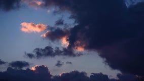 Nubes que vuelan a través del cielo azul, iluminado por los rayos del sol almacen de video