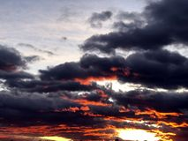 Nubes rojas ardientes durante puesta del sol del th imagenes de archivo