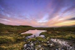 Nubes rojas en la puesta del sol con el cielo azul que refleja en una pequeña charca (Faroe Island) Fotografía de archivo