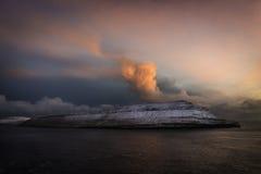 Nubes rojas encima de las islas cubiertas con nieve en la puesta del sol: Isla de Hestur, Faroe Island, Dinamarca, Europa Imagen de archivo libre de regalías