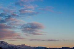 Nubes rosadas sobre picos sol-capsulados imagen de archivo