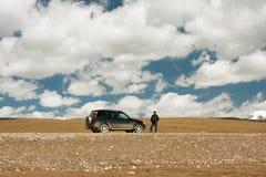 Nubes sobre el camino con el coche en el camino en una altitud de 4000 metros Fotos de archivo