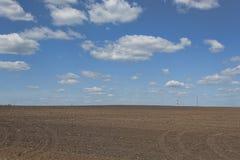 Nubes sobre el campo esa tierra en barbecho Imágenes de archivo libres de regalías