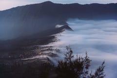 Nubes sobre el pueblo por la mañana contra el contexto de la montaña imagen de archivo