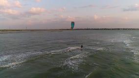 Nubes sobre la orilla, un montar a caballo del kitesurf del hombre en las ondas metrajes