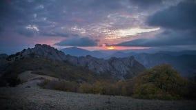 Nubes sobre las montañas en la puesta del sol almacen de video